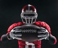 Futbolu amerykańskiego gracz pozuje z piłką na czarnym tle Zdjęcie Royalty Free