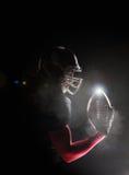 Futbolu amerykańskiego gracz pozuje z piłką na czarnym tle Zdjęcia Royalty Free