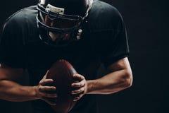 Futbolu amerykańskiego gracz z hełmem i zbroja z piłką przeciw czerni ścianie fotografia stock
