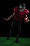 Futbolu amerykańskiego gracza opierać z ukosa z piłką w jeden jego ręka Fotografia Royalty Free
