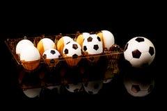 Futebóis entre os ovos brancos na bandeja do ovo Cápsulas do futebol na bandeja do ovo Tão aparece bolas de futebol imagens de stock royalty free