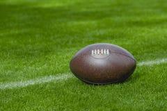 Futebol americano, bola de rugby no fundo do campo de grama verde imagens de stock