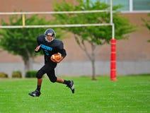Futebol americano da juventude que funciona para trás ir para ele Fotografia de Stock Royalty Free