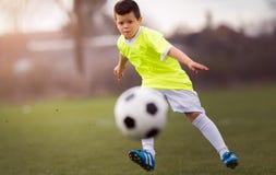 Futebol de retrocesso do menino no campo de esportes imagem de stock royalty free