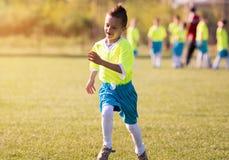 Futebol de retrocesso do menino no campo de esportes fotografia de stock royalty free