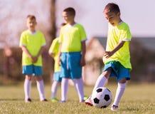 Futebol de retrocesso do menino no campo de esportes fotos de stock royalty free