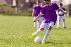 Futebol de retrocesso do menino no campo de esportes fotos de stock
