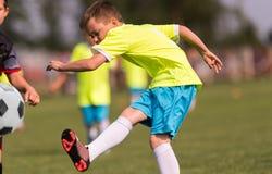 Futebol de retrocesso do menino no campo de esportes foto de stock royalty free