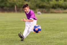 Futebol de retrocesso do menino no campo de esportes imagem de stock