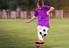 Futebol de retrocesso do menino no campo de esportes fotografia de stock