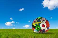 Futebol do futebol com as bandeiras de país isoladas na grama luxúria e no céu azul Campeonato mundial ilustração royalty free