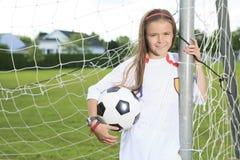Futebol do jogo da criança em um campo Foto de Stock Royalty Free