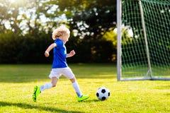 Futebol do jogo das crian?as Crian?a no campo de futebol fotografia de stock