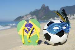 Futebol e Flip Flops da bola de futebol da máscara do carnaval na praia Brasil fotografia de stock royalty free