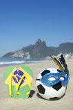 Futebol e Flip Flops da bola de futebol da máscara do carnaval na praia Brasil imagens de stock royalty free