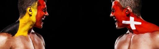 Futebol ou atleta do fan de futebol com bodyart na cara - bandeiras de Bélgica contra Suíça Conceito do esporte com copyspace Naç fotografia de stock