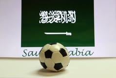 Futebol pequeno no assoalho branco e na bandeira saudita da nação com o texto do fundo de Arábia Saudita Imagens de Stock