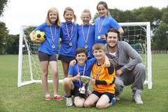 Futebol vitorioso Team With Medals And Trophy da escola imagem de stock