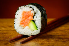 Futomaki sushi roll on chopsticks. Still life with futomaki sushi roll on chopsticks Stock Photography