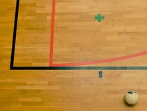 Futsal ball and red and black lines on hardwood sporting floor. Renewal wooden floor. Of sports hall with colorful marking lines stock photo