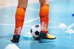 Futsal league. Indoor soccer player in futsal shoes training dribble drill with ball. Indoor soccer training. Running futsal player, soccer ball, white cones stock photo