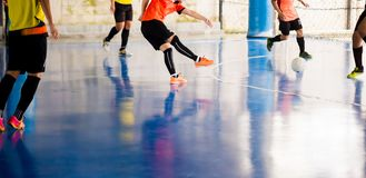 Futsal player trap and control the ball for shoot to goal. Soccer players fighting each other by kicking the ball. Indoor soccer stock photos