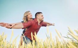 愉快的年轻夫妇获得乐趣在麦田在夏天,愉快的futu 免版税库存图片