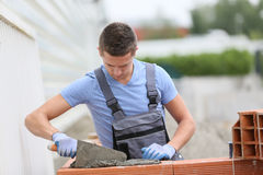 Futur brick layer working outside. Young brick layer working outside on brick wall construction Royalty Free Stock Photography