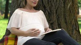 Futur livre de lecture de maman concernant nouveau-né, poussées de sentiment, arrangées la vie stressless banque de vidéos