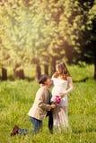 Futur papa se mettant à genoux à attendre la maman avec des fleurs à disposition Photographie stock libre de droits