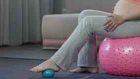 Futura mamá que se sienta en la bola de la aptitud, dando masajes a pies con la bola de goma, cuidado del cuerpo almacen de metraje de vídeo