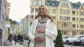 Futura mamma alla moda bionda che segna pancia, aspettativa di parto, felicità video d archivio