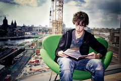 Future. Teenager reading a book in a library in front of a window overviewing the city .expressing building his future Stock Image