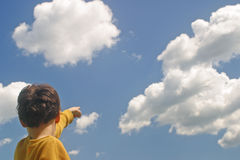 Into the Future. A boy pointing up at the clouds Stock Images