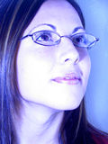 The Future. A blue toned photo of a young woman in glasses looking up towards a great future Stock Images