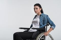 Pensive crippled woman touching wheelchair. Future ahead. Young budding crippled woman looking at the camera while using wheelchair and waiting Stock Images