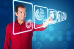 Future business interface solution. Business man in red shirt clicking on futuristic interface of hologram touch screens with graphs and charts on blue Royalty Free Stock Photography