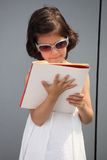 Future businesswoman. Child reading a book. Kid standing in front of an office building, wearing sunglasses and reading a book Royalty Free Stock Photo