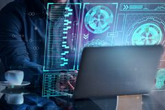 Future concept. Businessman hands using laptop placed on office desktop with digital business hologram and other items. Future concept. Double exposure Royalty Free Stock Photos