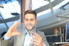 Future concept. Businessman holds futuristic transparent smart phone. Future concept. Businessman holds futuristic transparent smart phone stock photography
