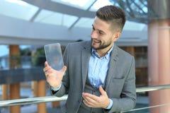 Future concept. Businessman holds futuristic transparent smart phone. Future concept. Businessman holds futuristic transparent smart phone stock photo