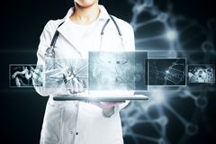 Future concept. Unrecognizable female doctor using tablet with digital medical interface on dark background with DNA. Future concept. Double exposure stock images