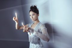 Future concept. Young pretty asian woman touching digital hologram. Young pretty asian female touching digital hologram screen. Future woman concept art. Fashion Stock Photos