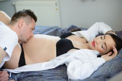 Future dad kissing the belly of his pregnant wife Royalty Free Stock Photo