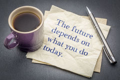 The future depends on what you do today. Inspirational quote - handwriting on a napkin with cup of coffee against gray slate stone background royalty free stock images