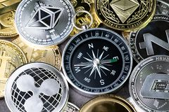Future direction or forecast of crypto currency price, compass w. Ith various of shiny silver and golden physical cryptocurrencies symbol coins, Bitcoin stock image