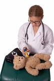 Future doctor. Cute little blond girl dressed up like a doctor holding a pretend needle and a brown teddy bear smiling stock photos