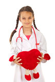 Future doctor girl holding heart toy stock photo