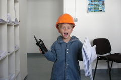 Future engineer. Cute smiling toddler with a helmet, a walkie-talkie and drawings in a construction site office royalty free stock photo
