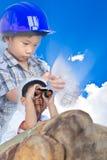 Future engineer, boy lying prone on a boulder and using binocula Royalty Free Stock Image